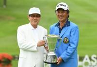昨年大会優勝の米山剛(右)にトロフィーを手渡す池森